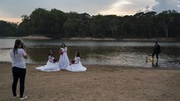 Eliene Pereira Francisco (tengah) berpose untuk foto untuk album pernikahan dengan putrinya Jaiane Pereira Marsal (kiri) dan Gislaine Pereira de Araujo dengan latar belakang hutan hujan Amazon di pantai sungai Jamanxim di Novo Progresso, Brasil (2/9/2019). (AP Photo/Leo Correa)