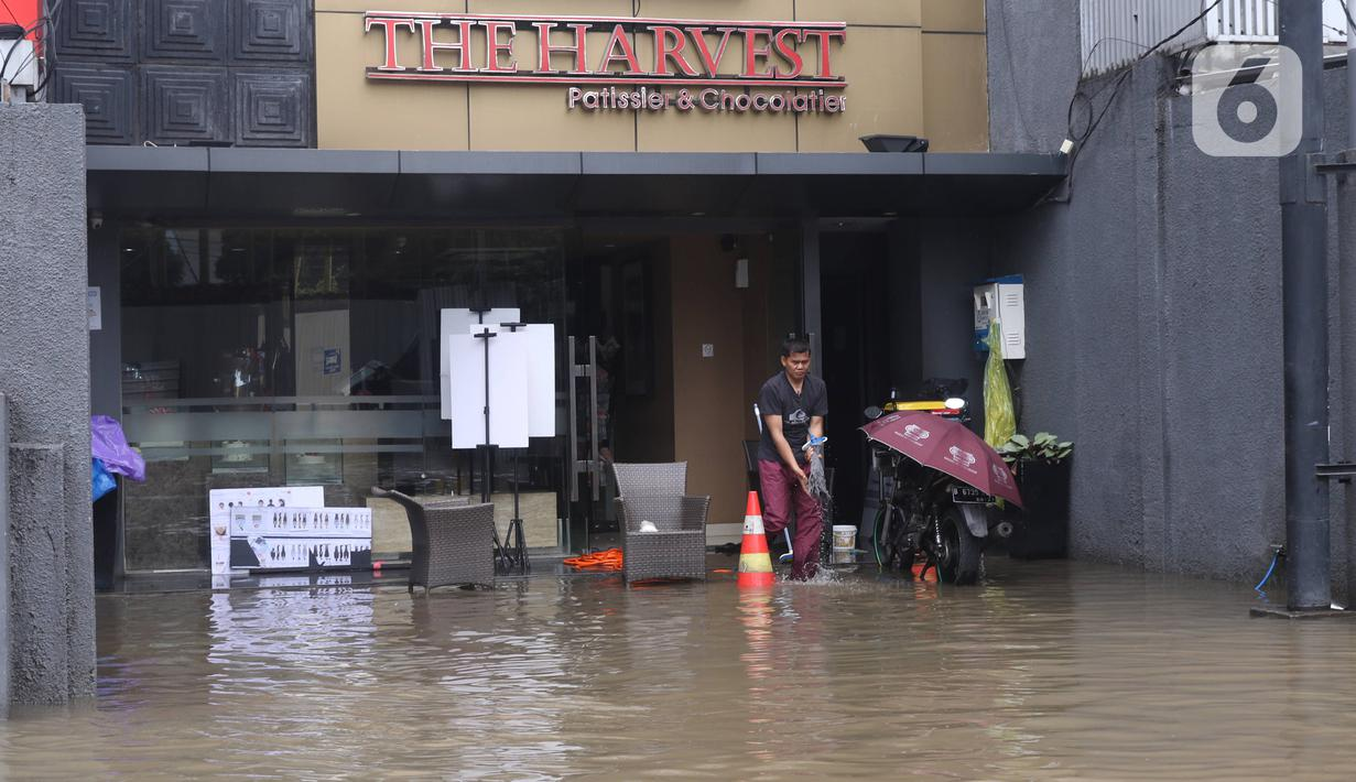Pekerja membersihkan pertokoan yang terendam banjir di Kawasan Bendungan Hilir (Benhil), Jakarta Pusat, Selasa (25/2/2020). Salah satu wilayah terdampak banjir yakni kawasan Benhil hingga membuat akses jalan untuk sementara terputus.  (Liputan6.com/Angga Yuniar)