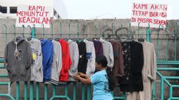 Pedagang sedang merapikan pakaian di kawasan luar pasar senen, Jakarta, Minggu (1/12/2019). Pedagang kaki lima di luar kawasan pasar senen menolak relokasi di pasar kenari, rencananya akan dipindahkan pada 1 Desember 2019 ini. . (Liputan6.com/Herman Zakharia)