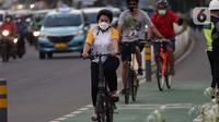 Warga mengenakan masker bersepeda di jalan Jenderal Sudirman, Jakarta, Jumat (25/6/2021). Hari ini Jumat (25/6), Provinsi DKI Jakarta mencatat penambahan kasus konfirmasi positif Covid-19 sebanyak 6.934 orang. (Liputan6.com/Helmi Fithriansyah)
