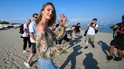Model Afrika Selatan Candice Swanepoel menyapa awak media sebelum sesi pemotretan di pantai Lido menjelang pembukaan Festival Film Venesia ke-76 di Venice Lido, Italia (27/8/2019). (AFP Photo/Vincenzo Pinto)