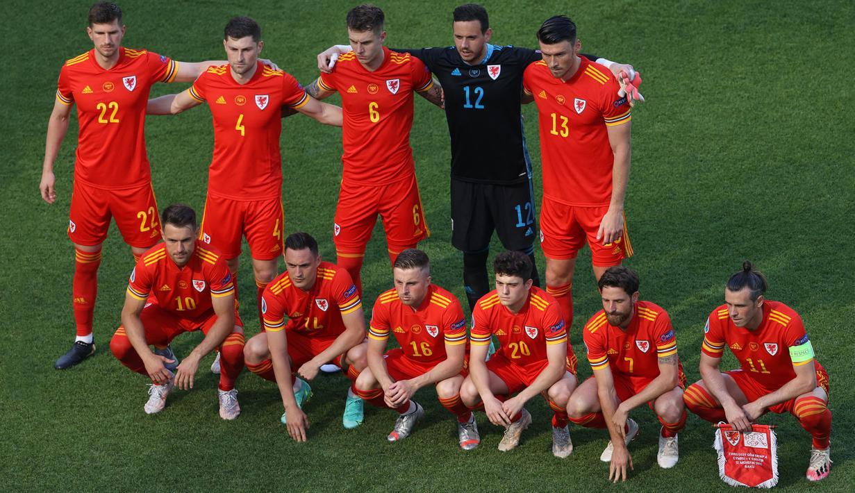 """Formasi """"berantakan"""" Timnas Wales mengundang perhatian kala mereka berjumpa dengan Timnas Swiss di laga perdana Grup A Euro 2020. Berbeda dengan pose tim pada umumnya, mereka dengan sengaja memilih bergaya asimetris dan terkesan berantakan. (Foto: AFP/Pool/Naomi Baker)"""