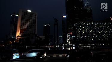 Sejumlah kendaraan melintas dengan kondisi jalan gelap tanpa penerangan akibat listrik padam di kawasan Bundaran HI, Jakarta, Minggu (4/8/2019). Pemadaman listrik serentak yang terjadi sejak Minggu siang mengubah suasana malam di ibu kota menjadi gelap gulita. (merdeka.com/Iqbal S. Nugroho)