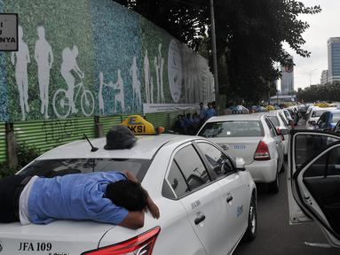 Seorang sopir tidur diatas bagasi taksi saat demo di depan Gedung DPR/MPR, Jakarta, Selasa (22/3). Selain melakukan demo, sopir taksi tersebut melakukan sweeping ke supir taksi yang beroperasi di dalam tol, dan membakar ban. (Liputan6.com/Johan Tallo)