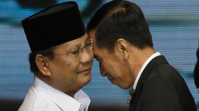 Dua calon Presiden Indonesia, Joko Widodo (Jokowi) dari Partai PDIP dan Prabowo Subianto dari Partai Gerindra saling merangkul selama sesi debat pilpres 2014 di Jakarta pada 9 Juni 2014. (AP Photo/Dita Alangkara)