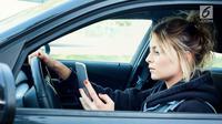 Ilustrasi menyetir sambil main ponsel (iStockPhoto)