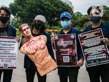 Sejumlah mahasiswa dari Universitas Trisakti menggelar aksi memperingati Hari HAM Internasional di depan Taman Aspirasi, Jakarta, Kamis (10/12/2020). Aksi tersebut menuntut agar pemerintah segera menyelesaikan berbagai permasalahan pelanggaran HAM berat di Indonesia. (Liputan6.com/Faizal Fanani)