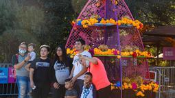 Sejumlah orang berfoto di depan berbagai dekorasi saat perayaan Hari Orang Mati di San Antonio, Texas, AS (2/11/2020). Hari Orang Mati adalah hari raya Meksiko yang melibatkan keluarga dan teman berkumpul untuk berdoa serta mengenang teman dan anggota keluarga yang telah meninggal. (Xinhua/Lie Ma)