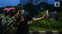 Seorang pendemo berselfie dengan anggota Marinir saat aksi menolak Omnibus Law UU Cipta Kerja di kawasan Patung Kuda, Jakarta, Selasa (20/10/2020).  Anggota Marinir membubarkan dan mengawal pulang massa pendemo  ke rumah masing-masing. (merdeka.com/Imam Buhori)