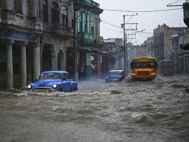 Mobil dan bus tua Amerika Serikat melewati jalan yang banjir di Havana, Kuba, 30 Juni 2021. Hujan deras dan selokan yang tidak berfungsi menyebabkan banjir di jalan-jalan di Havana. (YAMIL LAGE/AFP)