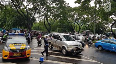 Petugas mengarahkan kendaraan yang melintasi kawasan SCBD usai balkon BEI ambruk, Jakarta, Senin (15/1). Ambruknya atap lobi balkon Bursa Efek Indonesia (BEI) membuat lalu lintas di sekitar SCBD macet. (Liputan6.com/Herman Zakharia)