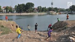 Anak-anak bermain di pinggir Waduk Ria Rio di kawasan Pedongkelan, Jakarta, Kamis (11/7/2019). Meski bertempat tinggal di atas lahan sengketa, anak-anak setempat memanfaatkan tanah kosong yang penuh semak belukar tersebut sebagai sarana bermain ketika sore hari. (merdeka.com/Iqbal S. Nugroho)