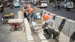 Aktivitas pekerja membuat separator jalan di kawasan Pasar Minggu, Jakarta Selatan, Rabu (23/10/2019). Pembuatan separator permanen tersebut merupakan bagian dari penataan kawasan Pasar Minggu agar lebih tertata dengan rapi. (Liputan6.com/Immanuel Antonius)