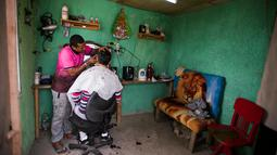 Seorang narapidana mencukur rambut narapidana lainnya di salah satu pangkas rambut yang berada di Penjara Punta de Rieles, Montevideo, Uruguay, 9 Mei 2019. Narapidana harus memiliki minimal enam bulan perilaku baik untuk bisa berbisnis di Penjara Punta de Rieles. (AP Photo/Matilde Campodonico)