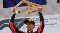 Pembalap Red Bull Max Verstappen dari Belanda mengangkat trofi di podium setelah memenangkan Grand Prix Formula Satu Austria di Red Bull Racetrack di Spielberg, Austria selatan, (1/7). Verstappen mencatatkan waktu 1:21:56,024. (AP Photo / Ronald Zak)