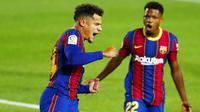 Penyerang Barcelona, Philippe Coutinho, melakukan selebrasi bersama Ansu Fati usai mencetak gol ke gawang Sevilla pada laga Liga Spanyol di Stadion Camp Nou, Minggu (4/10/2020). Kedua tim bermain imbang 1-1. (AP Photo/Joan Monfort)
