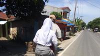 Foto perjuangan bapak mengantar anaknya ke sekolah dengan sepeda usang. Credit: Facebook/Rikie Hmd