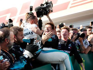 Pembalap Mercedes, Lewis Hamilton berselebrasi bersama timnya saat merayakan keberhasilnnya menjuarai GP Hungaria di Sirkuit Hungaroring, Mogyorod, (29/7). Hamilton berhasil menjuarai secara beruntun di musim ini. (AP Photo/Laszlo Balogh)