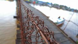 Kondisi kawat jembatan penyeberangan di Sungai Martapura, Banjarmasin, Kalimantan Selatan, Selasa (27/3). Walaupun menjadi jembatan satu-satunya untuk akses menyeberang warga sekitar, kondisi jembatan terlihat seadanya. (Liputan6.com/Immanuel Antonius)