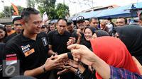 Cagub DKI Jakarta, Agus Harimurti Yudhoyono (kiri) menyalami warga saat sosialisasi di Jalan Menteng Tenggulun, Jakarta, Kamis (22/12). Agus bersosialisasi sambil berkeliling ke beberapa RW di kawasan tersebut. (Liputan6.com/Helmi Fithriansyah)