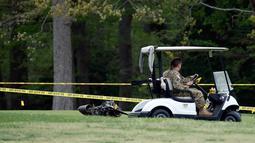 Penyidik memeriksa puing helikopter Blackhawk milik Angkatan Darat AS yang jatuh di lapangan golf di Maryland Selatan, Senin (17/4). Helikopter tersebut berputar sebelum jatuh di antara hole ketiga dan keempat di lapangan golf itu. (AP Photo/Alex Brandon)