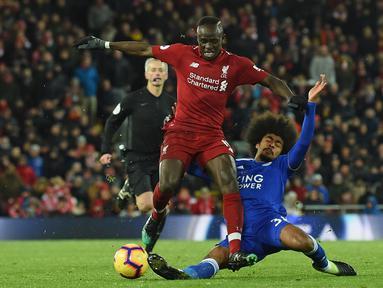 Aksi Sadio Mane usai dijegal Hamza Choudhury pada laga lanjutan Premier League yang berlangsung di stadion Anfield, Liverpool, Kamis (31/1). Liverpool imbang 1-1 kontra Leicester City. (AFP/Paul Ellis)