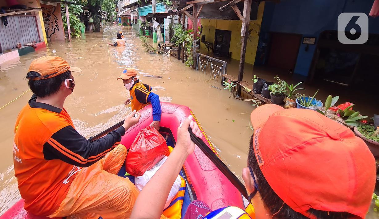 Petugas PPSU membawa bantuan nasi bungkus untuk warga yang bertahan saat banjir di kawasan pemukiman Jalan Bango, Pondok Labu, Jakarta Selatan, Sabtu (20/2/2021). Banjir akibat luapan Kali Krukut yang melanda sejak semalam menyebabkan pemukiman tergenang hingga dua meter. (merdeka.com/Arie Basuki)