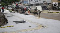 Kendaraan melintas di samping proyek revitalisasi trotoar di kawasan Senopati, Kebayoran Baru, Jakarta, Rabu (15/9/2021). Pemprov DKI Jakarta melalui Dinas Bina Marga merevitalisasi 10 ruas jalan di lima wilayah kota adminsitrasi Jakarta sampai akhir tahun 2021. (Liputan6.com/Herman Zakharia)