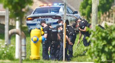 Sederet petugas polisi mencari bukti di lokasi kecelakaan mobil di London, Ontario pada Senin, 7 Juni 2021. Polisi mengatakan banyak orang tewas setelah beberapa pejalan kaki ditabrak mobil pada Minggu malam. (Geoff Robins/The Canadian Press via AP)