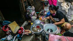 Warga membersihkan perabotan usai terendam banjir di permukiman kawasan Kampung Melayu, Jakarta, Selasa (9/2/2021). Banjir yang berangsur surut dimanfaatkan warga untuk membersihkan rumah dan barang-barang dari endapan lumpur. (Liputan6.com/Faizal Fanani)