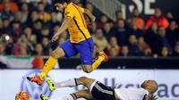 Striker Barcelona, Luis Suarez, melompati bek Valencia, Aymen Abdennour, pada laga La Liga di Mestalla, Valencia, Minggu (6/12/2015) dini hari WIB. (AFP/Jose Jordan)