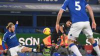 Gelandang Manchester City, Ruyad Mahrez (tengah) melakukan sepakan melengkung yang berujung gol untuk timnya ke gawang Everton, pada laga lanjutan Liga Inggris, di stadion Goodison Park, Kamis (18/2/2021) dini hari WIB.  (AFP / Jon Super)