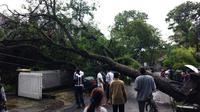 Pohon tumbang akibat hujan deras disertai angin kencang menghantam sedan di Kota Bandung. (Twitter/@farisahasnanto)