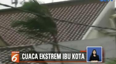 Sampah daun dan patahan atap rumah warga terbawa terbang oleh hembusan angin.