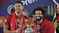 Pemain Liverpool Mohamed Salah (kanan) dan Dejan Lovren mengangkat trofi Liga Inggris usai bertanding melawan Chelsea di Anfield Stadium, Liverpool, Inggris, Rabu (22/7/2020). Penyerahan trofi Liga Inggris kepada Liverpool digelar tanpa penonton karena pandemi COVID-19. (Paul Ellis, Pool via AP)