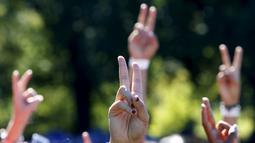 Sejumlah orang menunjukkan tanda perdamaian saat berkumpul untuk membentuk simbol perdamaian raksasa di New York Central Park , Selasa (6/10). Kegiatan yang diprakarsai janda Lennon, Yoko Ono itu menandai ulang tahun John Lennon ke-75.(REUTERS/Mike Segar)