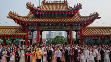 Pasangan pengantin baru keturunan Tionghoa  berfoto bersama seusai acara pernikahan massal di Kuil Thean Hou, Kuala Lumpur, Senin (9/9/2019). Upacara pernikahan massal diadakan untuk 99 pasangan pada hari kesembilan bulan kesembilan yang dianggap sebagai tanggal keberuntungan. (Mohd RASFAN / AFP)