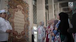 Kepala Protokol Masjid Istiqlal, Abu Hurairah menunjukkan kaligrafi Al-Quran kepada peserta Puteri Muslimah Asia 2018 di Mesjid Istiqlal, Jakarta, Kamis (3/4).  Kegiatan tersebut diikuti perwakilan sejumlah negara Asia. (Liputan6.com/Faizal Fanani)