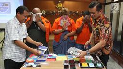 Kasubdit II Dirtippidsiber Bareskrim PolriKombes Pol Rickynaldo Chairul (kanan) saat rilis kasus penipuan melalui email di Jakarta, Jumat (16/11). Tersangka atas nama Ndubuike Gilber Ukpogu merupakan warga negara Nigeria. (Liputan6.com/AnggaYuniar)