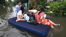 Warga menggunakan kasur karet ketika berusaha keluar dari pemukiman mereka yang terendam banjir di kawasan Periuk, Tangerang, Banten, Selasa (10/2). (ANTARA FOTO/Rivan Awal Lingga)
