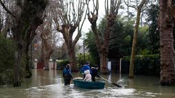 Seorang wanita menggunakan perahu membawa anak-anak di sebuah jalan banjir di Villennes sur Seine, sebelah barat Paris, (30/1). Meluapnya sungai Seine di Paris membuat kebun dan jalan terendam banjir. (AP Photo / Thibault Camus)