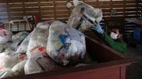 Pekerja mengumpulkan sampah yang telah dipisahkan di pusat limbah di Kamikatsu, Prefektur Tokushima, 14 Maret 2019. Kota di barat daya Jepang ini mengumumkan pada tahun 2003 bahwa pada tahun 2020 akan berhenti menghasilkan limbah sama sekali sebagai tujuan zero waste-nya. (Kazuhiro NOGI/AFP)