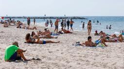 """Orang-orang bersantai di pantai di Tel Aviv, Israel, Minggu (18/10/2020). Israel """"dengan hati-hati dan bertanggungjawab"""" mulai melonggarkan kebijakan penutupan wilayah dan penghentian sebagian kegiatan atau lockdown, yang diberlakukan untuk mencegah merebaknya pandemi virus corona. (JACK GUEZ / AFP)"""