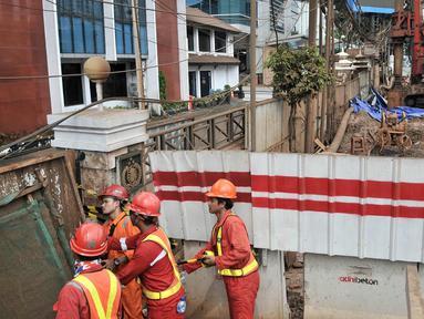 Pekerja dari Adhi Karya berada di sekitar lokasi kebocoran pipa gas bumi di depan Kantor BNN, Cawang, Jakarta, Selasa (13/3). Pascabocornya pipa gas bumi, aktivitas proyek LRT sementara dihentikan sementara. (Merdeka.com/Iqbal S. Nugroho)