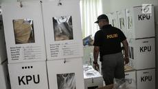 Polisi mengawasi kotak logistik hasil Pemilu 2019 di Kecamatan Menteng, Jakarta, Kamis (18/4). Komisi Independen Pemilihan (KIP) menargekan distribusi logistik hasil pemilu dari TPS ke tingkat PPK di daerah selesai dalam sehari dan dilanjutkan rekapitulasi pada 19 April. (Liputan6.com/Faizal Fanani)