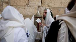 Sejumlah orang yang mengenakan penutup kepala dari kasta imam Yahudi berdoa menjelang Paskah di depan Tembok Barat, Yerusalem (13/4). Mereka melakukan upacara sebanyak tiga kali dalam setahun, yaitu Paskah, Shavuot dan Sukkot.  (AP Photo / Ariel Schalit)