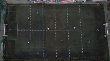 Sejumlah pria bermain sepak bola di klub lokal, Play Futbol 5, di Pergamino, Argentina, 1 Juli 2020. Demi bisa bermain di tengah pandemi Covid-19, klub membagi lapangan menjadi 12 persegi panjang untuk menandai area terbatas untuk setiap pemain, menjaga melakukan kontak fisik. (AP/Natacha Pisarenko)