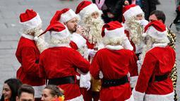 Sekelompok pria dengan kostum Santa Claus tiba di stasiun kereta api saat orang-orang menyambut dimulainya musim karnaval di jalan-jalan Kota Cologne, Jerman, Senin (11/11/2019). Kostum berbagai warna dan bentuk menambah suasana meriah di jalan-jalan dan tempat-tempat umum (AP Photo/Martin Meissner)