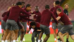 Para pemain Liverpool bercanda dengan rekan-rekannya selama sesi latihan di stadion San Paolo di Naples, Italia (2/10). Liverpool akan bertanding melawan Napoli pada grup C Liga Champions. (AFP Photo/Carlo Hermann)