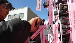Ibu dan aktivis menempatkan nama-nama wanita yang dibunuh di Ciudad Juarez pada sebuah salib hitam di Jembatan Internasional Paso del Norte, Ciudad Juarez, Chihuahua, Meksiko, Rabu (7/3). (HERIKA MARTINEZ/AFP)